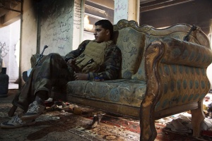 A Free Syrian Army fighter sits on a sofa inside a house in Deir al-Zor